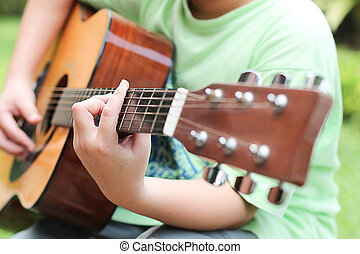 Young young Playing Guitar - Asian young boy learning to...