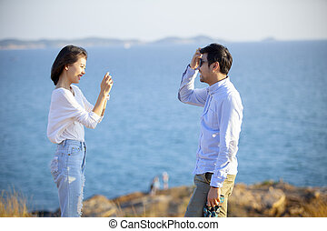 younger asian couples taking a photograph by smartphone with happiness emotion