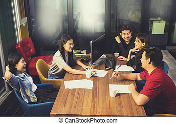 younger asian freelance team relaxing on working table in...