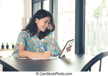 younger asian freelance woman looking to computer tablet screen and writing on white paper ,shot in home office
