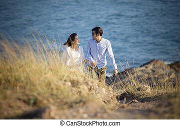 younger asian man and woman relaxing at vacation sea beach