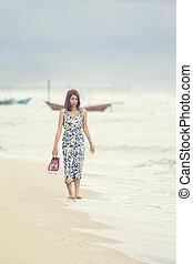 younger asian woman walking on sea beach