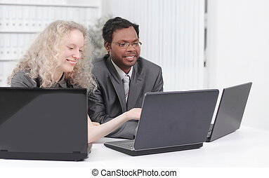 younger employees discussing business issues in office