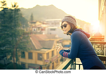 younger traveling woman standing outside building terrace and looking to destination scene against beautiful sun rise