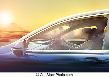 younger woman driving passenger car in urban against sunset sky city