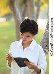 younger woman  reading book in park