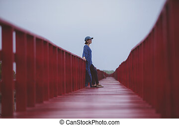younger woman standing on red wood bridge thailand