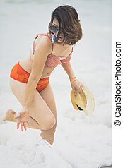 younger woman wearing bikini suit playing with happiness emotion on summer vacation beach