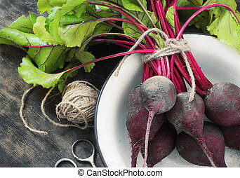 Young,fresh beets with tops on old wooden background.Style rustic.Selective focus