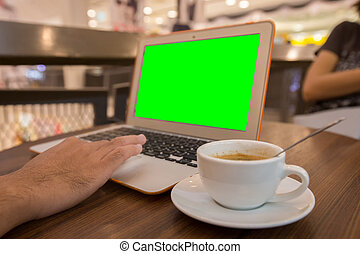 Youngman working with laptop in cafe, laptop with green screen.