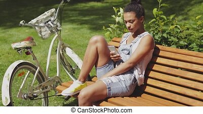 Youngster with smartphone and bicycle - Young casual woman...