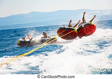 Younsters tubing - Group of four bouncing up over wake on...