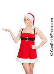 Your advertisement in her hand. Beautiful young woman in Santa costume holding a copy space and smiling while standing isolated on white