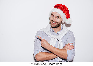 Your advertising here! Handsome young man in Santa hat pointing copy space and smiling while standing against white background