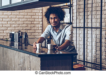 Your espresso! Young African man looking at camera with...