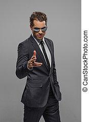 you?re, il, next!, fiducioso, giovane, uomini affari, in, occhiali da sole, standing, isolato, su, grigio, e, indicare, su, macchina fotografica