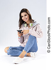Youth and Modern Lifestyle Concepts. Funny Laughing Caucasian Brunette Girl With Smartphone and a Pair of Headphones. Sitting on Floor Against White Background