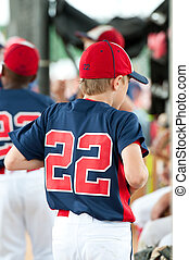 Youth baseball player in the dugout