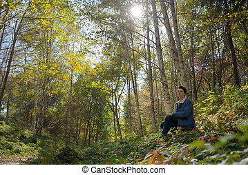 Youth boy alone in autumn forest