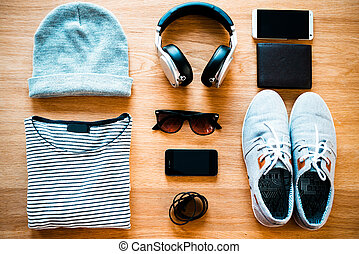 Youth collection. Top view of clothing and diverse personal accessory for teenagers laying on the wooden grain