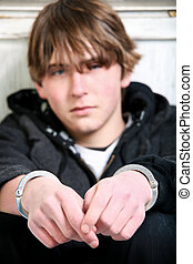youth crime - teenage in handcuffs against wall. Focus on...
