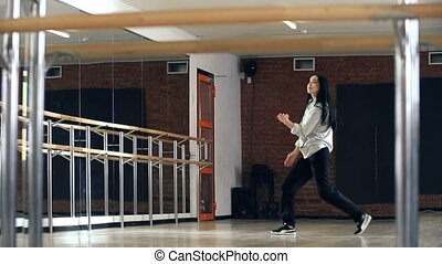 Youth Culture - Dolly shot of pretty Asian dancer practicing...