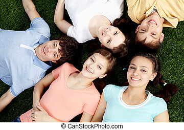 Youth - High angle view of five happy teens lying on grass
