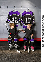 Two young boys fist pump before hockey game in dressing room