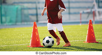 Youth soccer practice drills with cones. Soccer drills: slalom drill. Young football players training on pitch. Soccer slalom cone drill. Boy in red soccer jersey shirt running with ball between cones