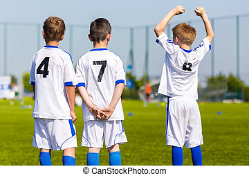 Youth sport team players support teammates on the sports competition