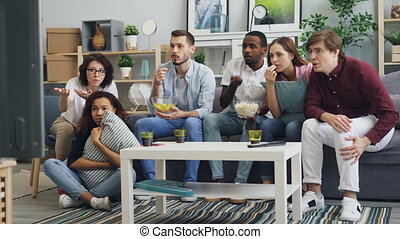 Youth watching tragic news on TV at home expressing negative...