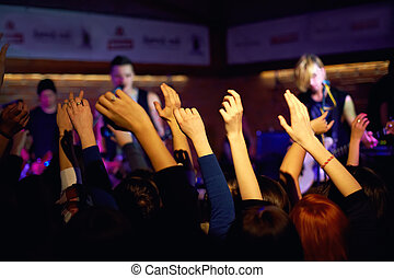youth waving hands on concert in night club