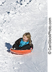 Youth - young girl sledding on a snowy slope.