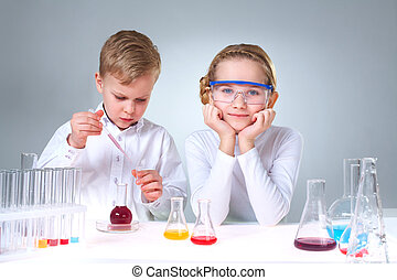 Youthful chemists - A little boy working with liquid and his...