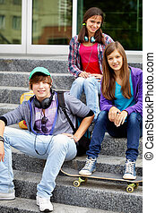 Youthful friends - Portrait of happy teens on stairs looking...