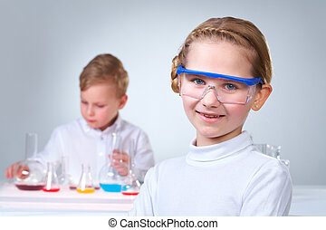 Youthful laborant - A little boy working with liquid with...