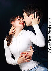 Youths fellow with a girl hug on the black background