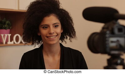 Young female mixed race model with afro hairstyle recording video