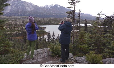 Yukon landscape with People hiking on travel living outdoor lifestyle. Travelers on hike taking photos at mountains landscape in autumn. Tourists from Alaska cruise ship excursion