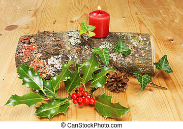 Yule log with lit candle holly and ivy