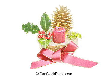 Yule log with red ribbon bow, seasonal foliage and a burning red candle
