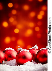 Yuletide sparkling out of focus light Christmas background with copy space. Red ornaments partially covered with snowflakes.