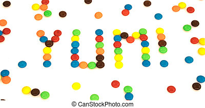 Yum word written with colorful button shaped chocolates candy isolated