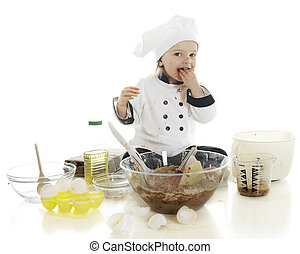 """An adorable preschool """"chef"""" tasting a fistful of the chocolate cake batter that she's been making. On a white background."""