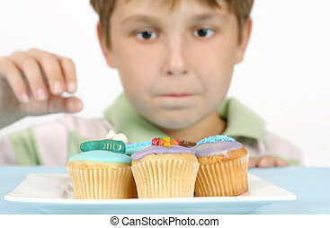 Yummy Cakes - This photo shows a boy eyeing off some cakes....