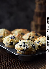 Yummy crumble top blueberry muffins in baking pan on black background with natural lighting copy space