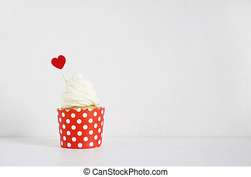 Yummy cupcake with red paper heart decoration on white table. Birthday, wedding or Valentine party food. Love concept.