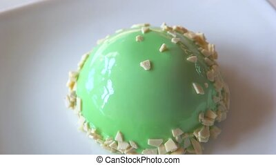 Yummy dessert with green glaze. Small green cake on plate....