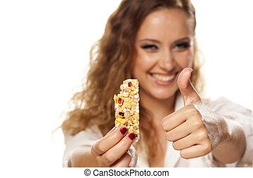 yummy fruit bar - smiling beautiful girl shows muesli bar ...