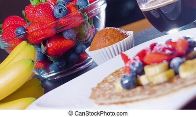 Strawberries, bananas and pancakes on the table